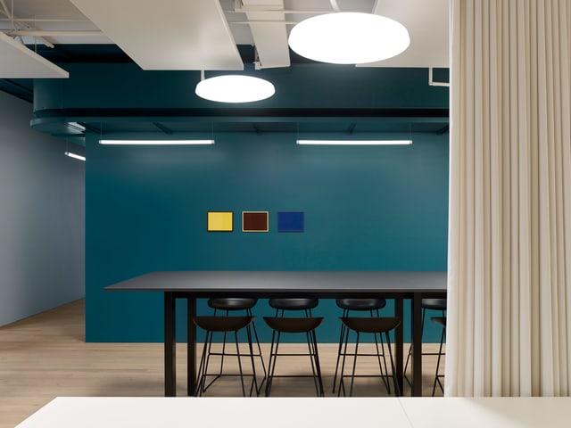 Sitzungstisch vor blauer Wand.