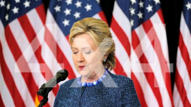 Hillary Clinton bei einer Rede vor einem Mikrofon. Im Hintergrund mehrere US-Flaggen.