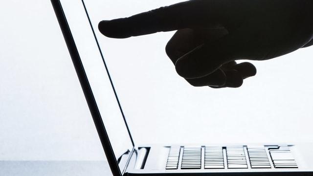 Ein Finger zeigt auf einen aufgeschlagenen Laptop.