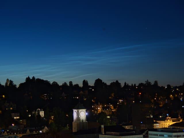 Silberne Wolken am Nachthimmel über der Stadt