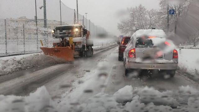 Auf einer Strasse fährt ein Pflug und räumt den Schnee weg.