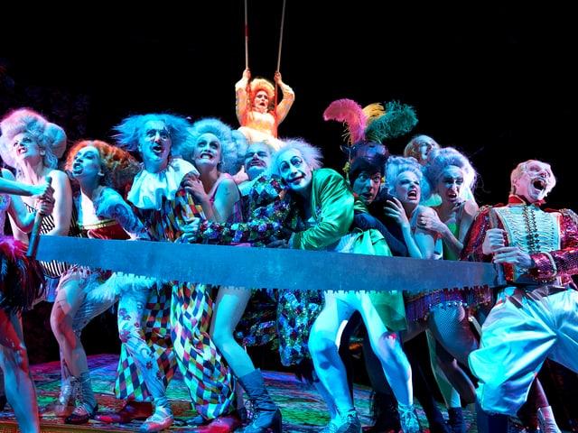 Als Zirkusartisten und Clowns verkleidete Schauspieler ziehen an einer Riesensäge.