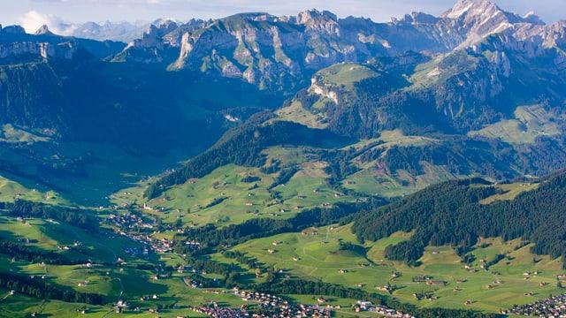 Landschaftsbild Berge und Häuser und grüne Wiesen