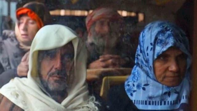 Zivilisten mit Kopftüchern sitzen in einem Bus.