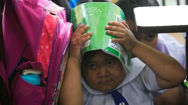 Ein Mädchen hält ein Buch über den Kopf.