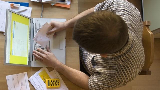 Ein junger Mann bezahlt eine Rechnung per Online-Banking