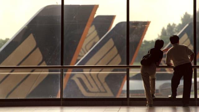 Zwei Menschen schauen aus Fenster auf Flügel von Flugzeugen.