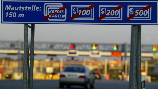 Maut-Schild über einer Autobahn, im Hintergrund die Mautstelle