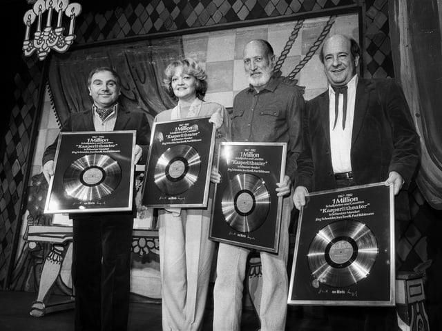 Drei Männer und eine Frau zeigen ihre Auszeichnung.