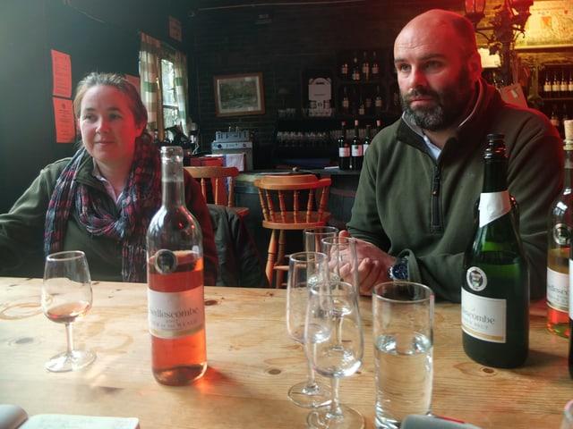 Eine Frau und ein Mann sitzen an einem Tisch, auf dem eine Weinflasche steht.