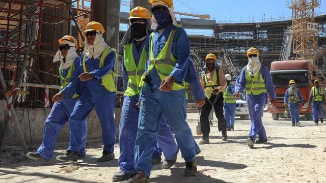 Ausländische Arbeiter verlassen eine Baustelle in Katar