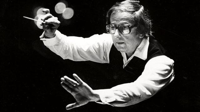 Ein Schwarz-Weiss-Bild von Andre Previn. Er hält einen Dirigentenstab.