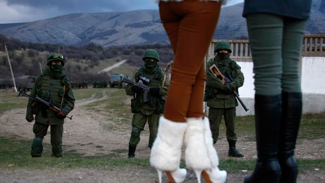 Zwei Frauen stehen vor bewaffneten Männern.