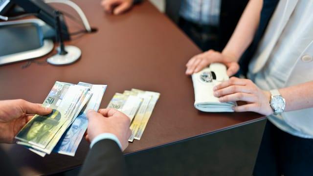 Geld wird abgezählt auf einem Bankschalter.