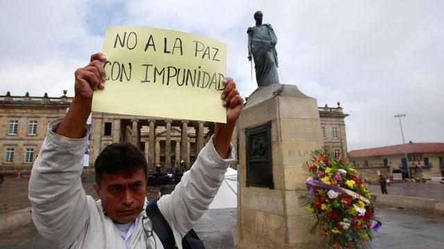 Ein Mann mit einem Transparent steht vor einem Kriegsdenkmal in Bogotà.