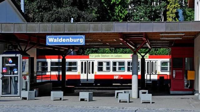 """Blick auf den Bahnhof Waldenburg mit dem Schild """"Waldenburg"""" und einem Zug der Waldenburgerbahn"""