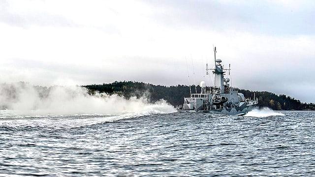 Aufklärungsschiff der Schwedischen Marine zieht eine lange Rauchfahne hinter sich her.