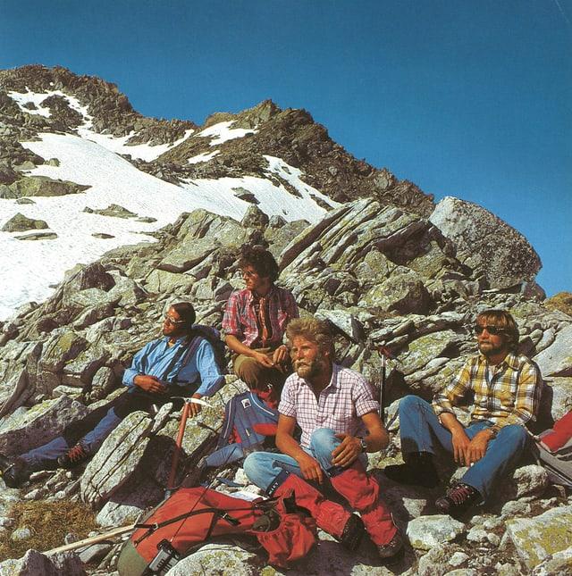 Die vier Alpinisten sitzen in den Bergen auf ein paar Felsen und ruhen sich aus.