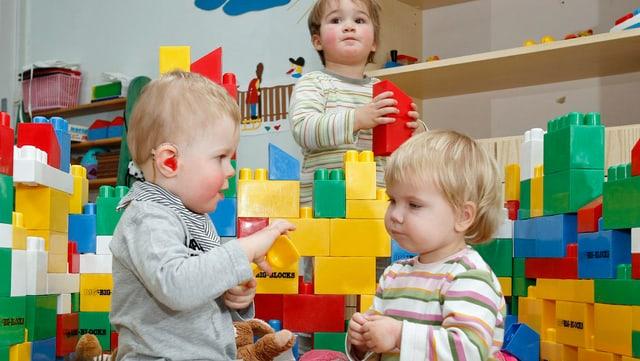 Drei Kleinkinder bauen eine Legomauer und spielen in einer Tagesstätte zusammen