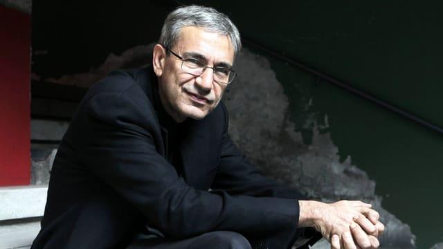 Schriftsteller Pamuk sitzt auf einer Treppe und schaut in die Kamera.