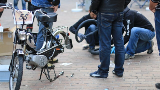 Trais participants da la tura midan in pneu d'in moped avant la partenza