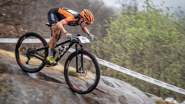 Frau fährt mit Mountainbike über Felsen