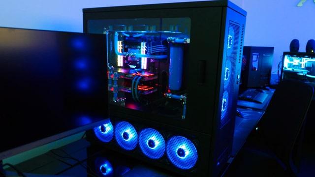 Ein abgedunkelter Raum, der in blauen Farben leuchtet und diverse PCs mit blauen LEDs die leuchten.