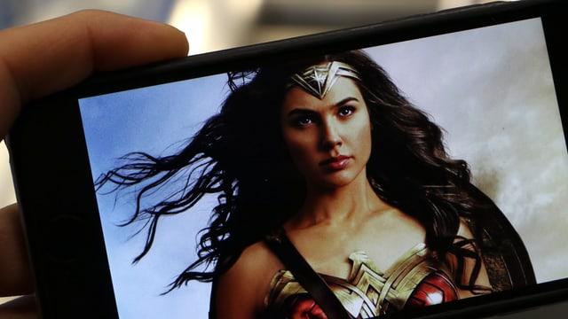 Eine Frau mit langen Haaren auf einem Smartphone.