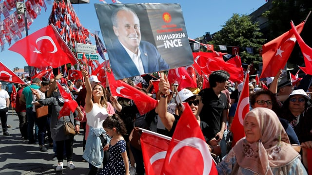 Menschenmenge schwenkt Türkei-Fahnen und Plakate mit Ince-Porträts.