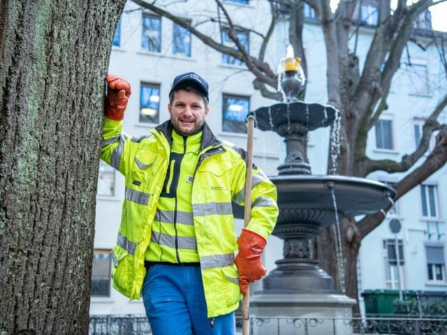 Oliver D'Agostini lehnt sich vor einem Brunnen an einen Baum