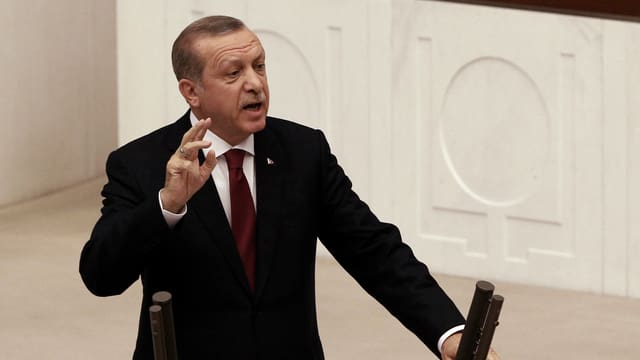 Purtret da Erdogan davant il pult da pledader en il parlament.
