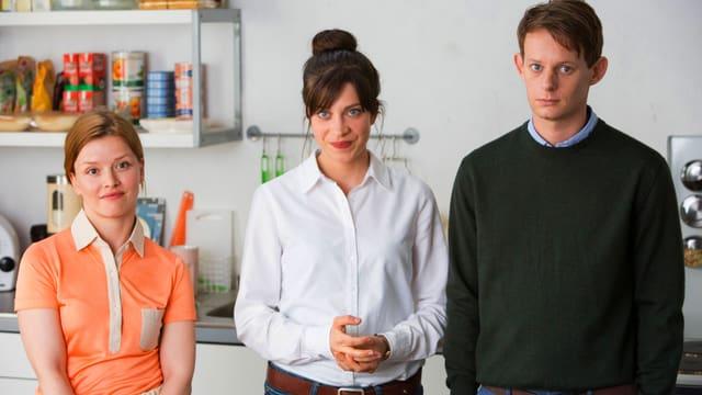 Drei junge Leute stehen in einer Küche.