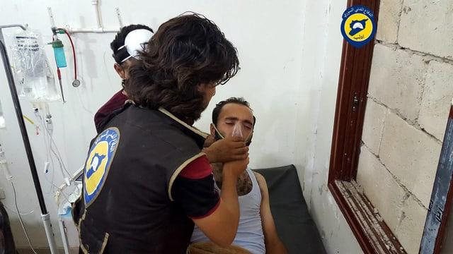 Mann im Spital erhält von einem Sanitäter eine Sauerstoffmaske.
