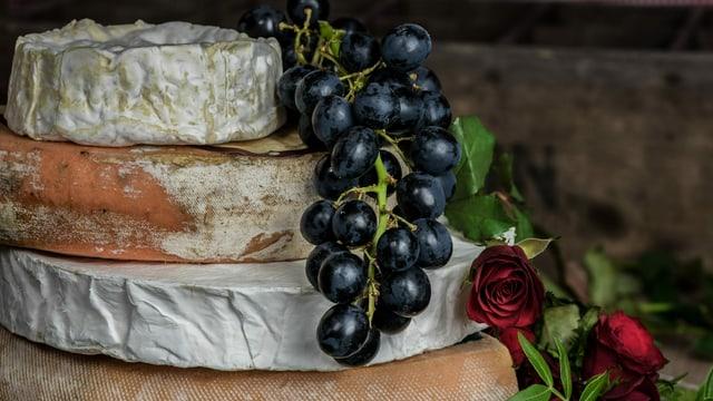 Vier zu einem Turm aufeinandergestellte Käselaibe. Als Dekoration Trauben und Rosen.