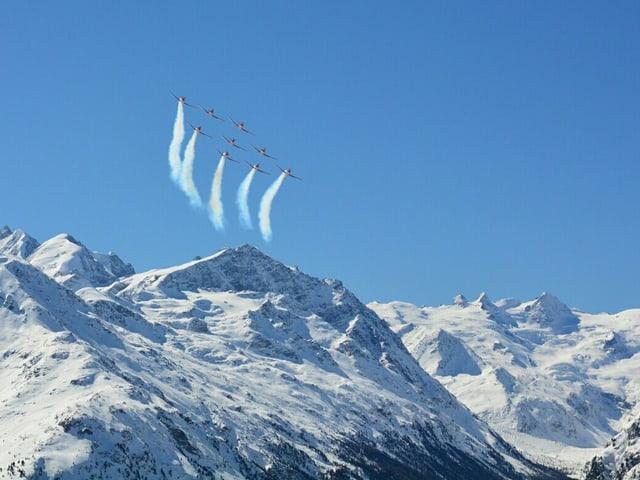 Der Himmel ist wolkenlos und die verschneiten Berge strahlen. Am Himmel ziehen 9 Militärflugzeuge 5 Rauchschwaden hinter sich her.