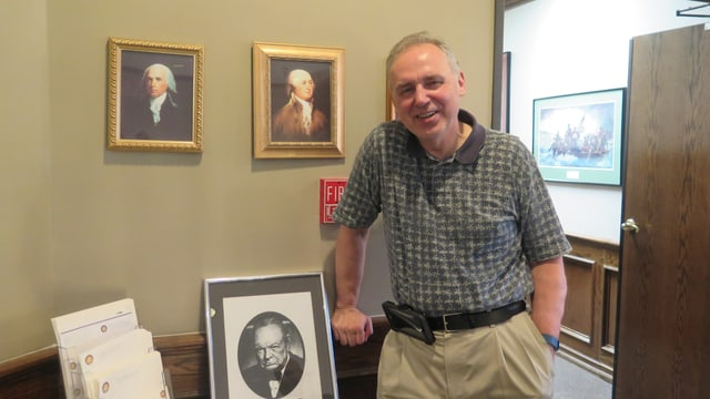 Bill Voegeli vor zwei Gemälden an einer Wand.