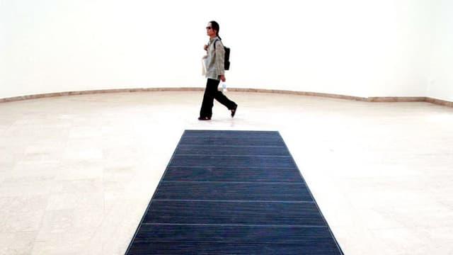 Heller Raum. Ein Museumsbesucher läuft an eine Gitter im Boden vorbei.