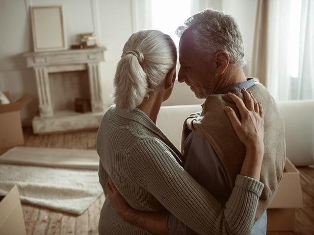 Ein älteres Paar in einer Wohnung mit Umzugskartons.