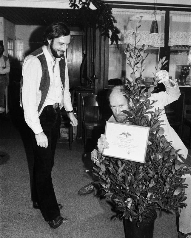 Zwei Männer und eine Topfpflanze