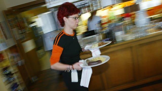Eine Serviceangestellte eilt mit zwei vollen Tellern durch ein Restaurant.