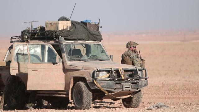 Jeep in der Wüste, daneben steht ein Mann in Kampfmontur.