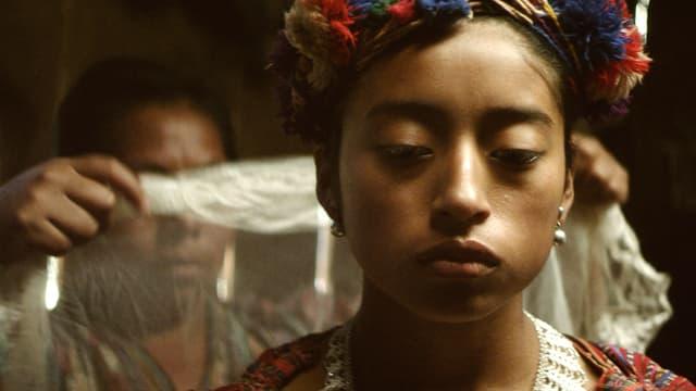 Eine junge Frau, die traurig aussieht. Hinter ihr, hält eine Frau ein weisses Tuch hoch.