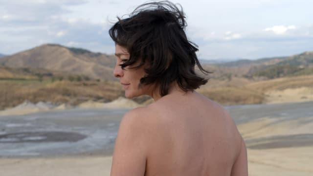 Eine Frau läuft nackt am Strand.