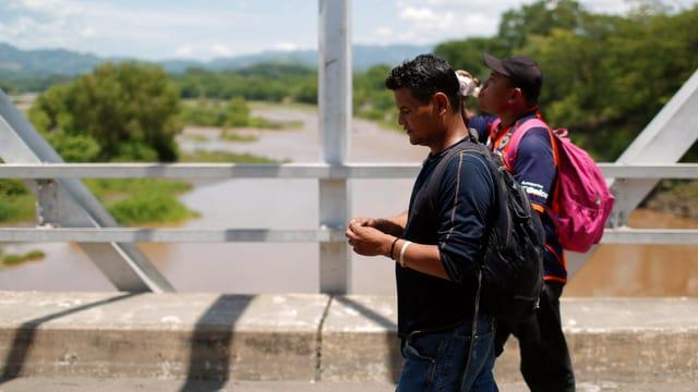 Zwei Jugendliche mit Rucksäcken auf einer Brücke an einem Fluss.
