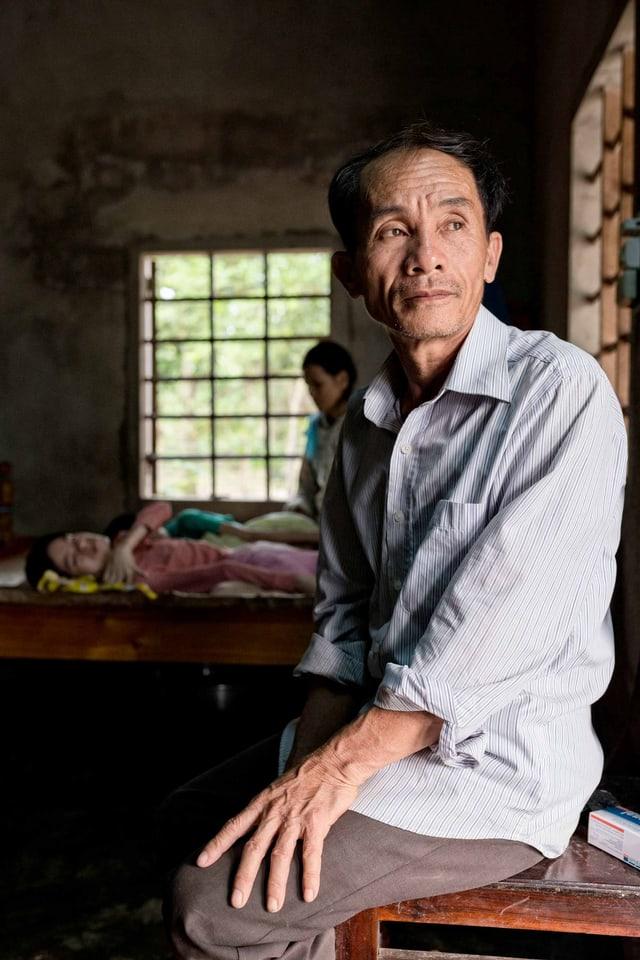 Sitzender Mann, im Hintergrund seine kranken Kinder.