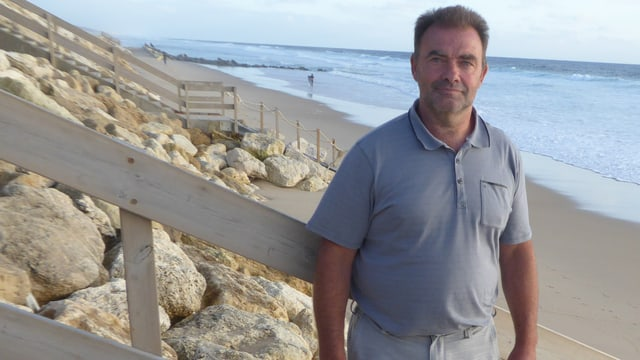 Ein Mann steht am Strand