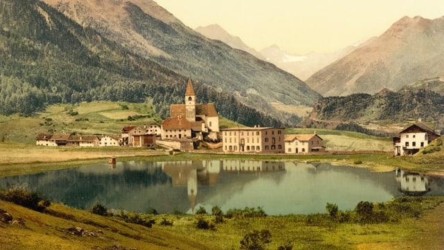 Blick auf ein kleines Dorf am Rand eines Sees. Im Hintergrund Berge.