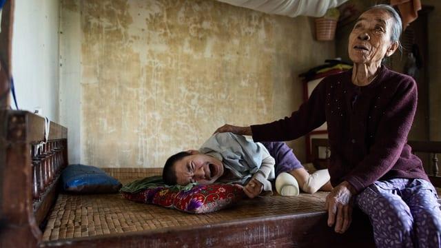 Ein gelähmter Junge liegt auf einer Art hartem Bett, daneben eine sorgenvoll blickende ältere Frau, die ihn streichelt