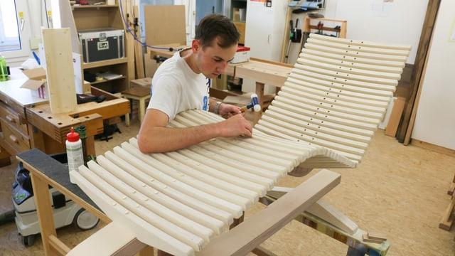 ein junger Mann baut ein Liegestuhlgerüst aus Holz