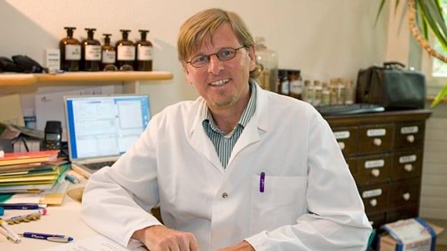 Dr. Frank Locher in der Praxis am Schreibtisch.